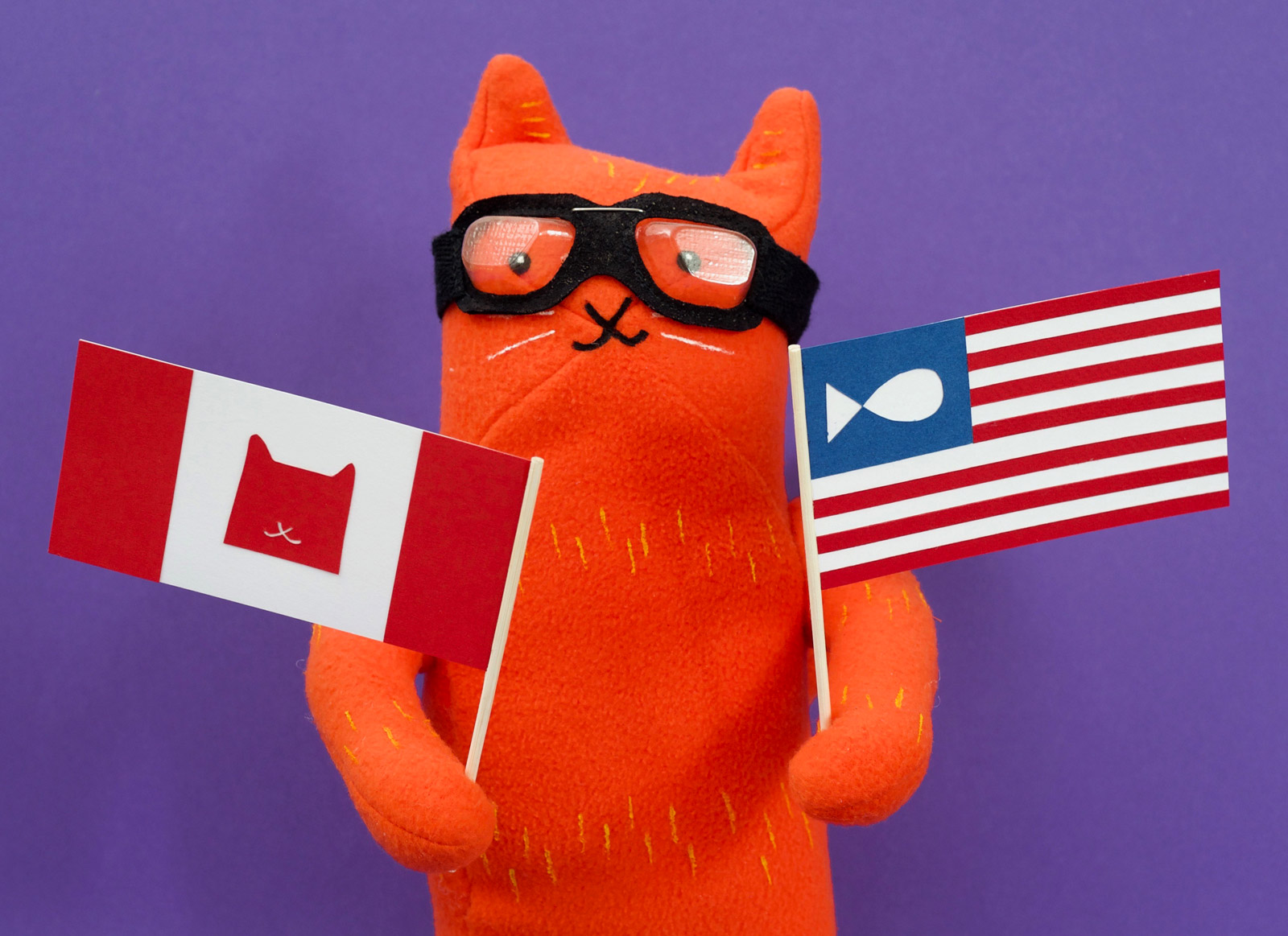 Plush Asta from Alley Cat Rally holding Canadian and USA flags